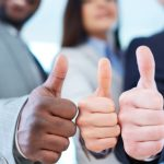 Three business partners keeping thumbs up
